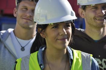 Kvinne med hjelm og gul arbeidsvest i forkant av to menn med hjelm